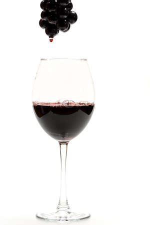 Glass of tasty dark red wine and bunch of black grapes isolated on white background, side view