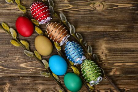 painted easter colorful eggs decorated with bright color threads and beads with willow, osier tree branch on wooden background , spring holiday celebration Stock Photo