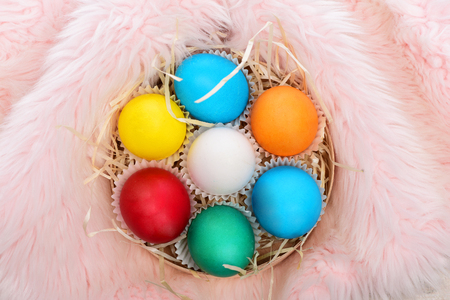 easter colorful eggs painted in bright colors with straw nest in wooden box on pink fur background, spring holiday celebration Stock Photo