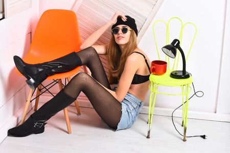 pretty woman or sexy cute girl with long blonde hair and adorable happy face in sunglasses, bra, hat, sits at orange and light green chair with lamp and red tea cup on white background