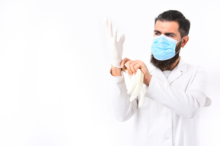 Bearded man, long beard. Brutal caucasian doctor or unshaven hipster, postgraduate student in mask and medical gown wearing gloves isolated on white studio background. Medicine concept