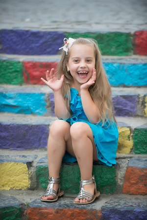 small happy baby girl or cute child with adorable smiling face and bow in blonde hair in blue dress outdoor sitting on colorful stony stairs background