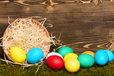 easter colorful eggs painted in bright colors with straw nest in wooden box on wood background with green moss, spring holiday celebration, copy space