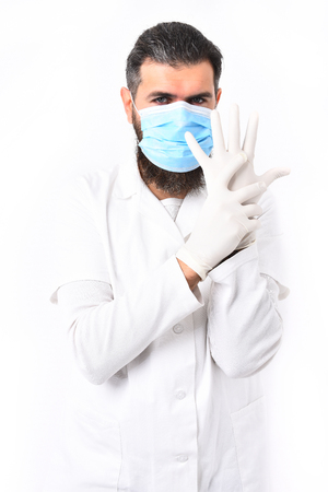 postgraduate: Bearded man, long beard. Brutal caucasian doctor or unshaven hipster, postgraduate student in mask and medical gown wearing gloves isolated on white studio background. Medicine concept