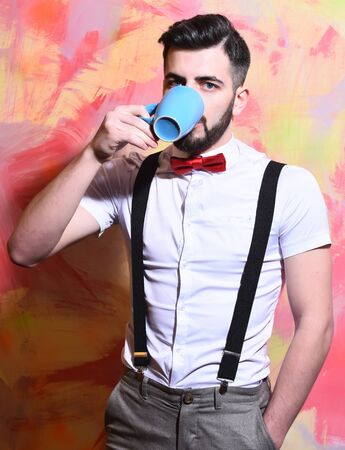 reggicalze: bearded man, long beard, brutal caucasian hipster with moustache in white shirt and suspenders with bow-tie drinking tea or coffee from blue cup with serious face on on colorful studio wall background Archivio Fotografico
