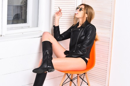pretty woman or sexy cute girl with blonde hair and adorable face smoking cigarette in black sunglasses, boots and leather jacket on body, sits at orange chair on white studio background near window Stock Photo