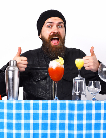 Bearded man, long beard. Brutal caucasian smiling happy hipster with moustache in rock black style and alcohol shot, fresh cocktail with bar stuff on blue checkered plaid isolated on white