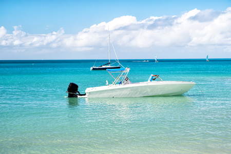 yachtsman: traveling and vacation, sport and sailing, man, yachtsman on motorboat, yacht on sea, ocean water, coast sunny summer outdoor on blue cloudy sky background in St. John, Antigua