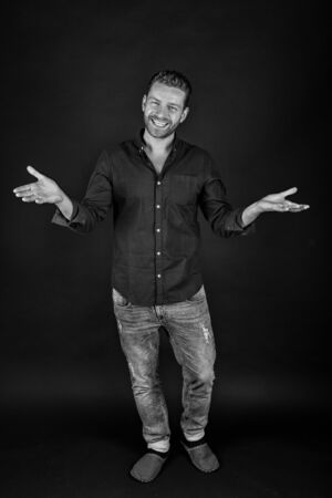 handsome happy man or sexy guy with beard on smiling face in fashionable shirt and jeans in studio, black and white
