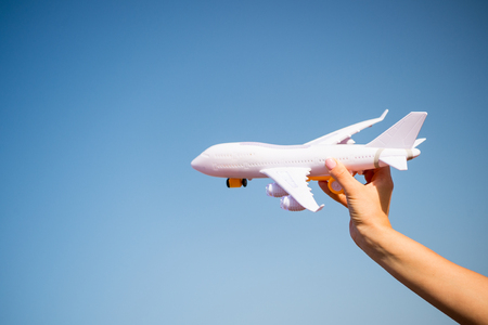 white toy plane in female hand on sunny blue sky background. business traveling and vacation. freedom and inspiration. airmail and postal delivery concept, copy space