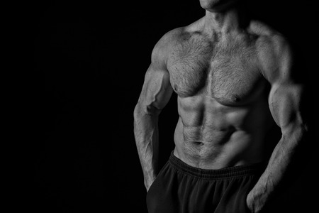 handsome bodybuilder man or sexy muscular guy with athlete body, torso and chest training sport and posing in gym, black and white, copy space