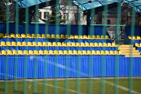 empty yellow and blue football stadium tribune behind fence of ukrainian educational training complex with green grass sunny outdoor for players team and match. sport and hobby Stock Photo