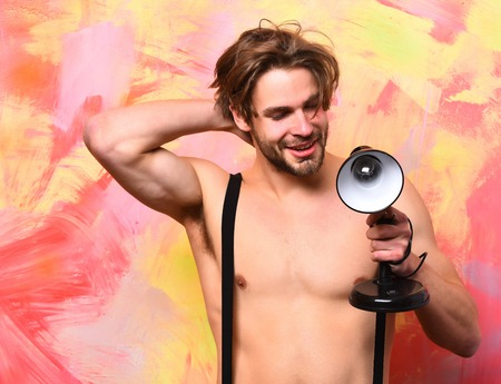 sexi: Bearded man, short beard. Caucasian smiling happy sexy macho man with moustache shows six packs and abs on muscle torso in pants with suspenders holding lamp on colorful studio background