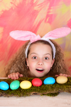 surprised easter girl in bunny ears, small child with curly hair, colorful painted eggs on moss on abstract background, womens or mothers day, spring holiday, childhood and happiness