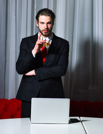 sexi: bearded man, businessman, long beard, brutal caucasian hipster with moustache with glass of whiskey has serious face, unshaven guy with stylish hair in suit and red tie works at laptop, computer