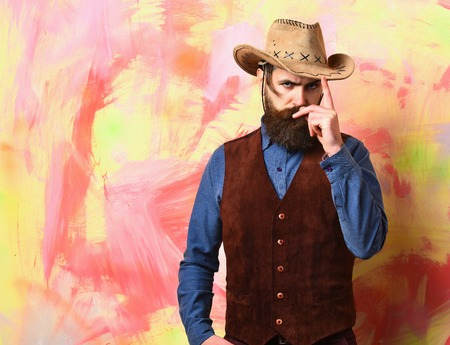 corrects: Bearded man, long beard. Brutal caucasian serious unshaven hipster corrects cowboy hat in vintage shirt and leather vest on colorful studio background, copy space