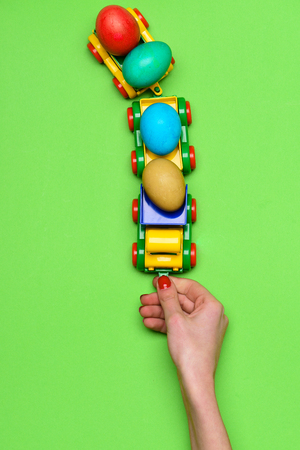 happy easter, import and export, farming and industry, transport, female hand of girl playing with plastic toy truck or lorry car with colorful handmade painted eggs on green background