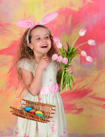 colorful painted eggs in basket, small child, happy easter girl in pink bunny ears with curly hair and smiling face, tulip flowers bouquet on abstract background, womens or mothers day, spring holiday