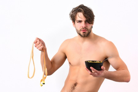 Bearded man, short beard. Caucasian sexy macho with stylish hair, moustache on serious face shows muscular torso holding black bowl with pasta and measuring tape isolated on white studio background