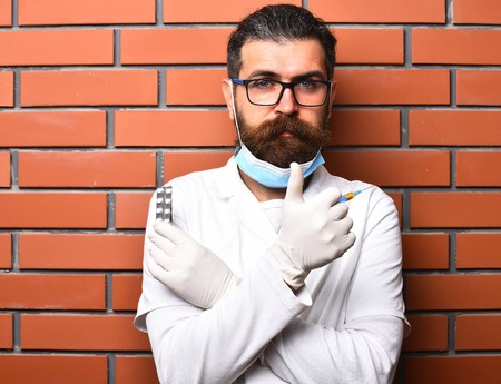 postgraduate: Bearded man, long beard. Brutal caucasian doctor or unshaven hipster, postgraduate student in medical gown, gloves holding syringe and pills on brown brick wall studio background. Medicine concept