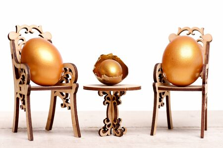 healthy food, golden eggs in broken shell, easter food painted in gold metallic color on wooden chair at table isolated on white background, eating and cooking, menu design, luxury and success