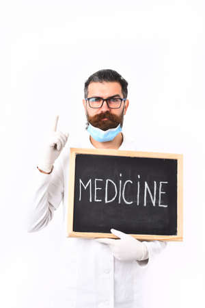 postgraduate: Bearded man, long beard. Brutal caucasian doctor or unshaven hipster, postgraduate student in mask, medical gown holding board isolated on white studio background. Medicine concept