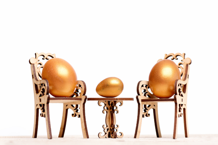 golden eggs, easter food painted in gold metallic color on wooden chair at table isolated on white background, healthy food, eating and cooking, restaurant, menu design, luxury and success, retirement Stock Photo