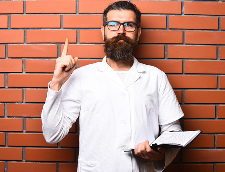 postgraduate: Bearded man, long beard. Brutal caucasian doctor or unshaven hipster, postgraduate student holding notebook with pen in medical gown and glasses on brown brick wall studio background. Medicine concept
