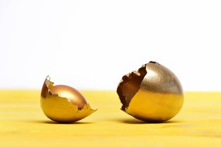 birth concept, golden broken egg with shell, eggshell, easter food painted in gold metallic color on yellow wood isolated on white background, future life, luxury and success, business and finance