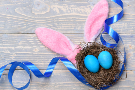 set of traditional eggs painted in blue color inside nest with ribbon and pink rabbit ears on grey vintage wooden background. Happy Easter concept