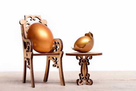 eating and cooking, healthy food, golden eggs in broken shell, easter food painted in gold metallic color on wooden chair at table isolated on white background, menu design, luxury and success