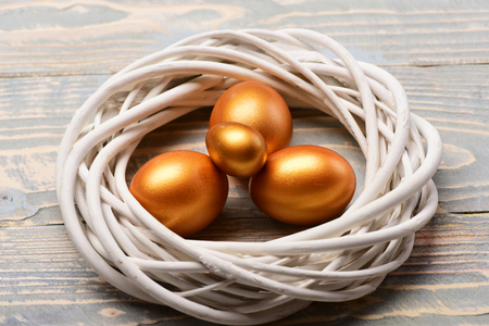 future life and birth, easter painted handmade golden eggs in white decorative bird nest on wooden background, happy easter concept, cooking and eating, traditional spring holiday decoration Banco de Imagens - 75751182