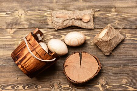 spoon on burlap, tree stump near wooden bucket or pail with beige wood eggs, happy easter concept, healthy food, farming and agriculture, future life and childhood, cooking and eating Stock Photo