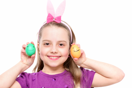 them: small baby girl or cute happy child wearing rabbit pink ears with purple blouse and playing with colorful easter eggs with funny faces on them isolated on white background