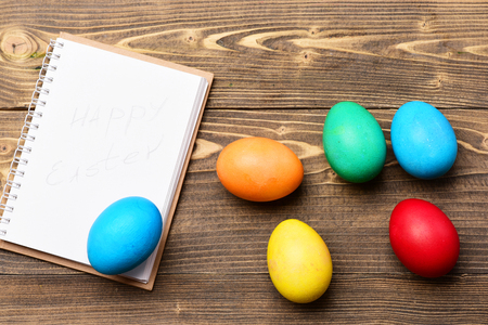 cooking and eating, colorful painted eggs, paper notebook on wooden background, happy easter, recipe and menu design, healthy food, farming and agriculture, drawing and art, copy space