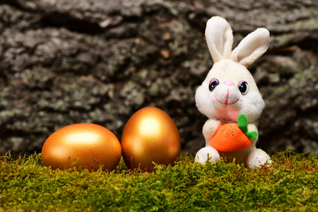 rabbit toy with carrot, traditional golden eggs metallic color on green moss on tree bark background, happy easter, farming, agriculture, luxury and success, riches, treasure, retirement, antique art