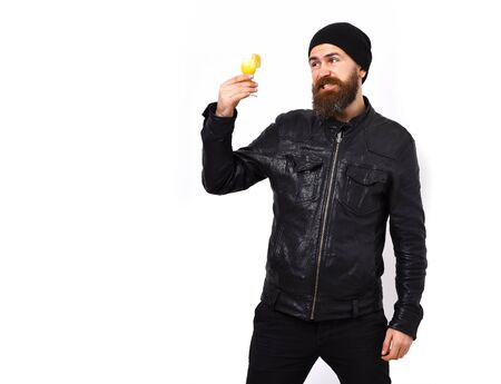 Bearded man, long beard. Brutal caucasian dissatisfied hipster with moustache holding glass of alcoholic beverage or shot in rock black style isolated on white studio background