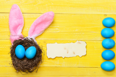 papel quemado: set of traditional eggs painted in blue color in nest with burnt paper and pink rabbit ears on yellow vintage wooden background. Happy Easter concept, copy space