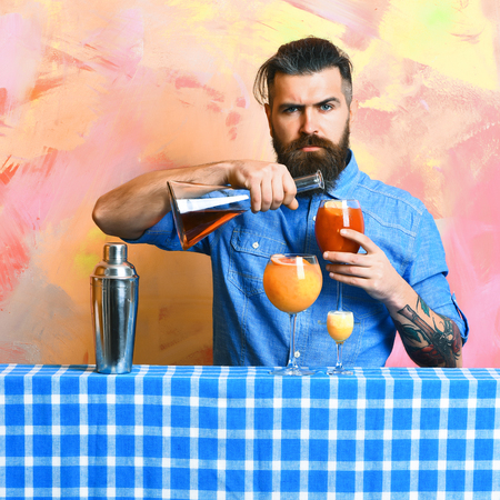 Bearded man, long beard. Brutal caucasian hipster with moustache in denim shirt doing cocktails or beverage and alcohol shot with bar stuff on blue checkered plaid on colorful texture background