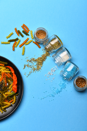 White salt crystals, spices and herbs spilled from glass jars and dried fusilli, colorful pasta, on black plate on blue background. Ingredients for cooking vegetarian or italian food Stock Photo