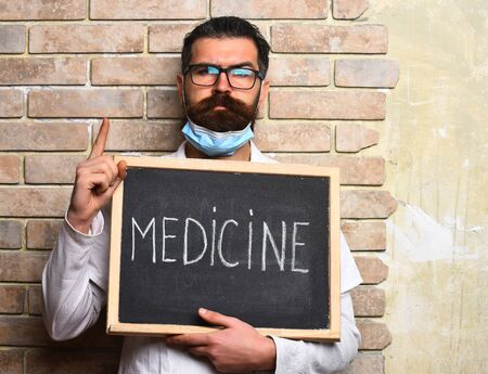 postgraduate: Bearded man, long beard. Brutal caucasian doctor or unshaven hipster, postgraduate student holding board with Medicine inscription in medical gown, glasses on beige brick wall studio background