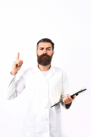 postgraduate: Bearded man, long beard. Brutal caucasian doctor or unshaven hipster, postgraduate student holding clipboard in medical gown isolated on white studio background. Medicine concept