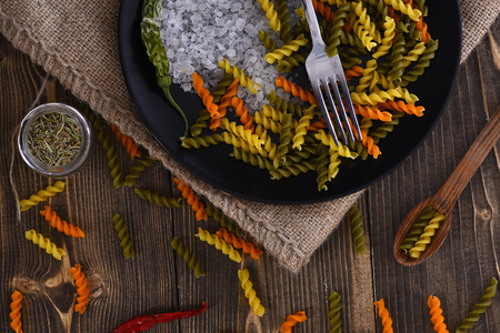crystal background: Colorful dried fusilli pasta, salt crystals and fork in black bowl on sackcloth, red peppers, spices in jar, spoon on brown wooden background. Ingredients for cooking vegetarian or italian food