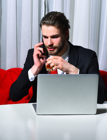 haircut: bearded man, businessman, long beard, brutal caucasian hipster with moustache holding glass with whiskey has happy face, unshaven guy with stylish hair in suit and red tie works at laptop, computer