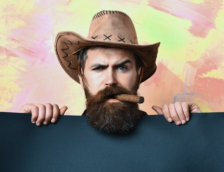 haircut: Bearded man, long beard. Brutal caucasian serious unshaven hipster in vintage cowboy hat with blue paper sheet and cigar in studio on colorful background Stock Photo