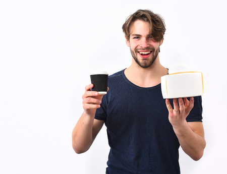 haircut: Bearded man, short beard. Caucasian sexy young macho with stylish hair and moustache on smiling happy face holding male box with coffee cup in blue shirt isolated on white studio background Stock Photo