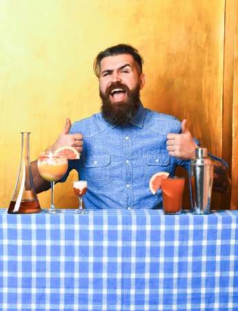 stuff: Bearded man, long beard. Brutal caucasian smiling happy hipster with moustache in denim shirt and alcohol shot, fresh cocktails with bar stuff on blue checkered plaid on golden texture background