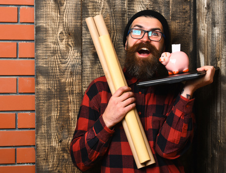 haircut: Bearded man, long beard. Brutal caucasian happy unshaven hipster holding craft paper rolls, piggy bank on laptop in checkered shirt with hat and glasses on brown vintage wooden studio background Stock Photo