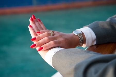Mani femminili e orologio da polso con il manicure rosso e anello d'oro al dito con diamanti in prossimità di acqua Archivio Fotografico - 76474267