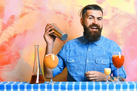 stuff: Bearded man, long beard. Brutal caucasian smiling hipster with moustache in denim shirt doing cocktails in shaker and alcohol shot with bar stuff on blue checkered plaid on colorful texture background Stock Photo
